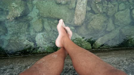 фут : Young man relaxes feet swinging over lake water surface, POV Стоковые видеозаписи