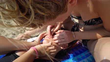 čelo : Teens cleaning face acnes on beach during summer vacation