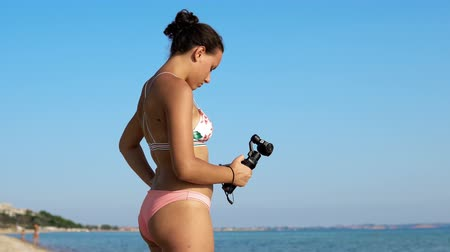 videocamera : Girl in bikini record video with new gadget, 3d stabilized gimbal camera osmo Stock Footage