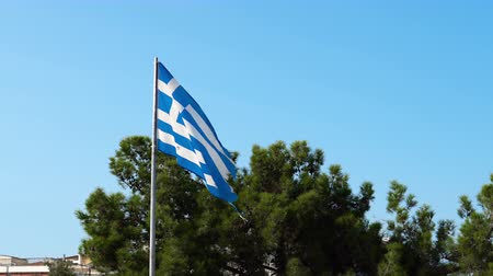 Эгейский : Torn old greek flag wave on beach agains blue sky