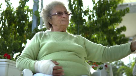 yaşlılar : elderly old woman with injured hand drinking coffee outdoor sitting Stok Video