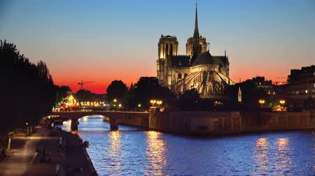 parisian : Cathedral of Notre Dame and riverside of Seine river in Paris at twilight sunset, France, background loop