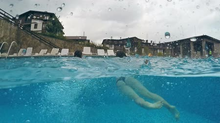 пловец : Two girls splashing in pool with legs at rainy weather, gopro dome half underwater view, SLOW MOTION