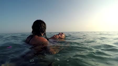 косички : Two happy girls play drowning game in sea water surface at sunset, slow motion