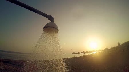 cákanec : Summer beach shower water pouring down against sunset sun, SLOW MOTION Dostupné videozáznamy