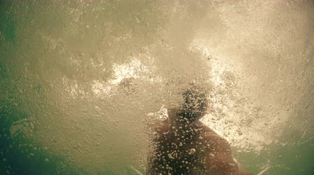 nadador : Underwater view from below of drowning man trying to save making fast moves and bubbles with hands against sunset