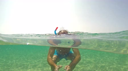 mergulhador : Man put snorkeling mask and swim on sea water surface, camera half underwater view