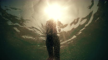 surf : Underwater pov view of sexy fashion model walking in sea backlit by summer sunset sun