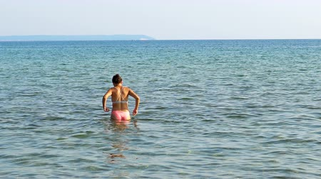 vstoupit : Female teen enter sea water, summer beach refreshment