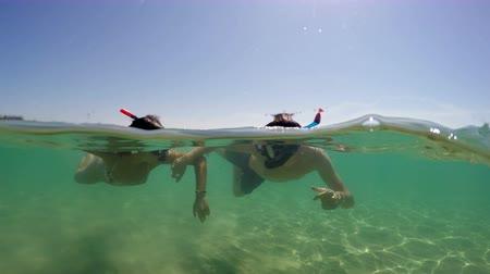 plavat : Beautiful young couple having fun at sea snorkeling, camera dome shot