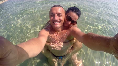 turkuaz : Selfie of romantic happy couple relaxing in turquoise beach water. Summer holiday concept