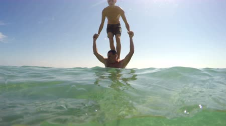 backflip : Teen makes backflip jump from his father shoulder in sea on summer vacation, camera dome shot