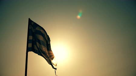 greek flag : Old torn Greek flag waves against summer sunset sun Stock Footage