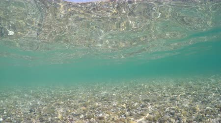 小石 : Fish pov swimming in sea shallow water with stone, pebble floor and reflection on water surface, underwater view 動画素材