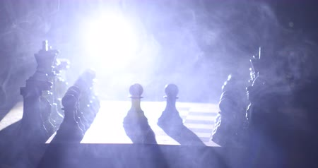 xadrez : Chess board game concept of business ideas and competition and strategy ideas concept. Chess figures on a dark background with smoke and fog. Selective focus Vídeos
