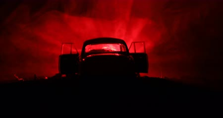фронт : Silhouette of old vintage car in dark foggy toned background with glowing lights