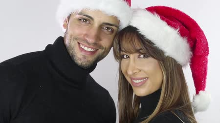 casal heterossexual : Christmas holiday happy couple wear red new year santa hat cap, man and woman love smile looking at camera kissing