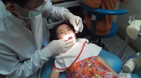 Little girl opening his mouth wide during inspection of oral cavity