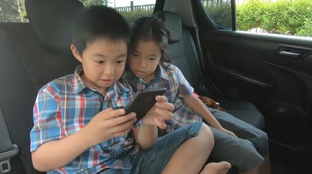 плюшевый мишка : happy little boy girl wearing seatbelts hold smartphone in car