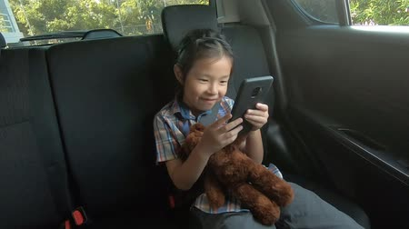 happy little girl wearing seatbelts hold smartphone in car Wideo