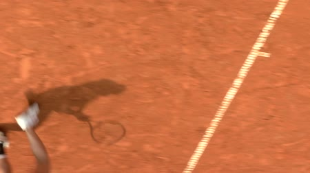 отскок : Shadow of a tennis player during serve motion in a clay court