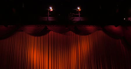 stage theater : A closed red stage curtain in a theater