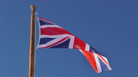 anglia : UK flag in slow motion on blue sky Stock mozgókép