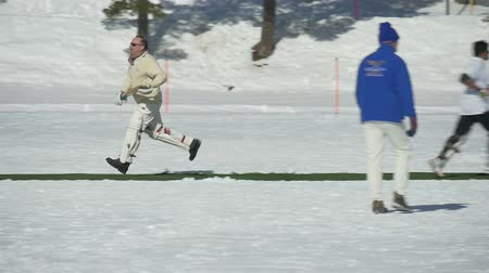 подача : A cricket batsman making a run in a cricket match during Cricket on Ice in St. Moritz (Switzerland) on 18th February 2016 - slow motion