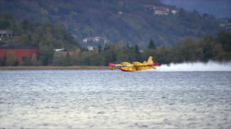 ação : Pusiano, Italy - October 2017: Firefighting aircraft Canadair refilling from the lake during the fire emergency in the mountains near Como
