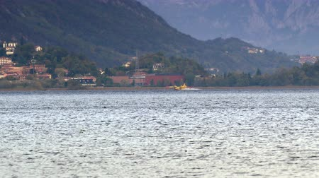 vészhelyzet : Pusiano, Italy - October 2017: Firefighting aircraft Canadair refilling from the lake during the fire emergency in the mountains near Como