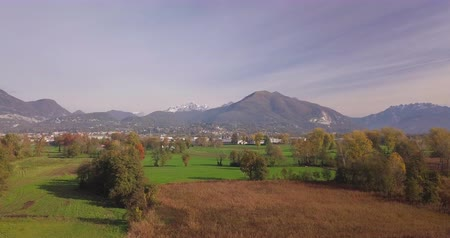 tyč : Aerial view of an autumn lowland landscape in northern Italy, dry cane thickets growing along the banks of a small lake and Alps in background.