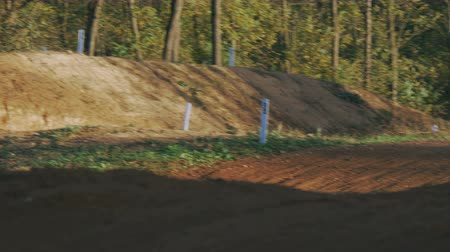 enduro : Motocross riders jumps and takes off over the track Stock Footage