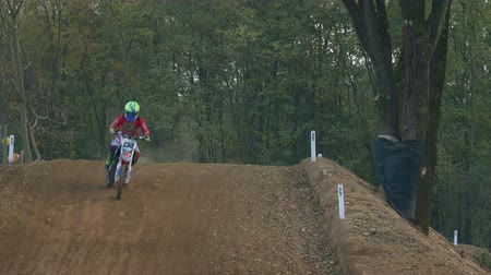 enduro : Young racer on dirt bike motorcycle jumps and takes off over the track Stock Footage