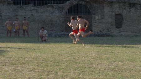 старомодный : Ancient roman pentathlon athletes run the 'stadion' (a short foot race) in slow motion during the reenactment 'Back In Time' on July 29, 2017 in Arezzo (Italy)