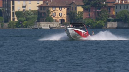 "tow : A young boy riding wakeboard on wave of motorboat during the ""Wake Zone Cup"" on 1 July 2108 in Lake Como (Italy) Stock Footage"