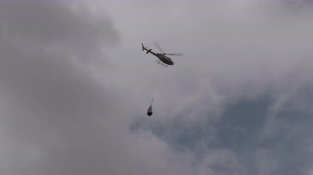 döner : A firefighting helicopter flying in a cloudy sky Stok Video