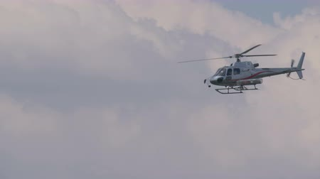 brancard : A rescue helicopter with stretcher flying in a cloudy sky