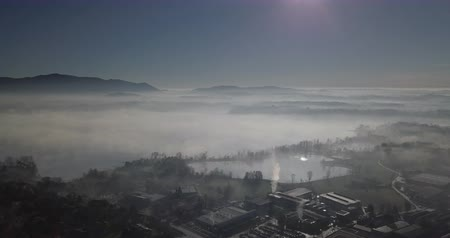 daleko : Aerial view of a fog-covered valley in the morning, rural landscape and industrial plants emerge from the fog