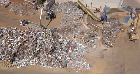 Aerial view of a crane grabbing metal scrap from a dump.