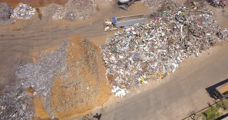 wozek : Aerial view of a crane grabbing metal scrap from a dump.