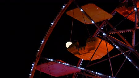 luna park : A colored ferris wheel with moon in background in an amusement park at night, Como (Italy)
