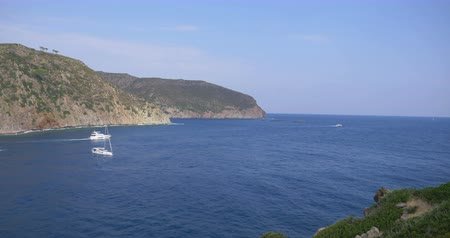 Yachts and sailboats in the blue sea of the Capraia Island in the Mediterranean Sea Стоковые видеозаписи