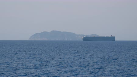 Car and truck carrier vessel passes in front of a small island in the Mediterranean Sea Стоковые видеозаписи