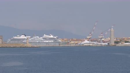 Cruise ships and cranes behind the breakwater in the port of Livorno, Italy