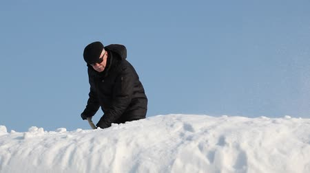 deep snow : Man removing snow from a roof with a snowshovel