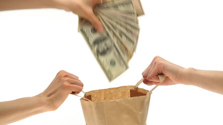 seguro : Hand throwing money into the paper bag on white background