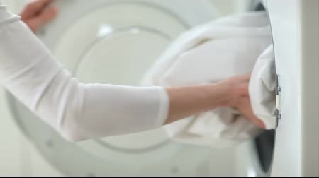 çamaşırhane : Female hand putting white linen into washing machine and then taking it out