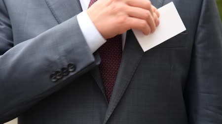 odznaka : Businessman in formal suit taking blank business card off Wideo