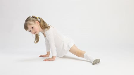 капелька : Smiling little girl doing the splits on white background