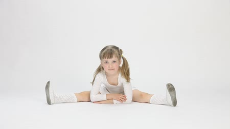 девчушки : Smiling little girl doing the splits on white background